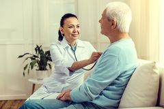 Smiling nurse listening to heart beating of retired patient. Let me check. Selective focus on a cheerful mature lady smiling while looking at a senior gentleman royalty free stock photos