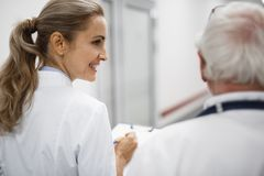 Smiling nurse looking at doctor while they walking in hospital hallway royalty free stock photography