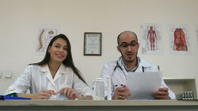 Smiling nurse and male doctor talking to the camera stock video footage