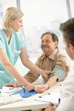 Smiling nurse measuring blood pressure of patient. Smiling nurse measuring blood pressure of elderly patient, smiling at doctor's desk Royalty Free Stock Photography
