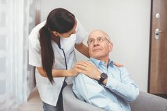 Smiling nurse and old senior man patient at home. Smiling nurse and old senior men patient at home. Care for older people concept stock image