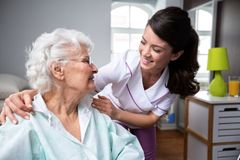 Smiling nurse and old woman patient at wheelchair. Smiling nurse and old women patient at wheelchair at private nursing home Royalty Free Stock Photo