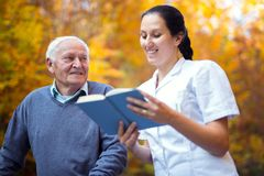 Smiling nurse reading book to senior man. Smiling nurse reading book to senior men that uses walker with caregiver outdoor Stock Photos