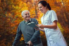 Smiling nurse reading book to senior man. Smiling nurse reading book to senior men that uses walker with caregiver outdoor Stock Photo
