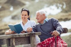 Smiling nurse reading book to senior man. Outdoor Royalty Free Stock Photos