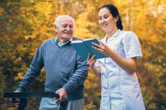 Smiling nurse reading book to senior man that uses walker. Smiling nurse reading book to senior men that uses walker with caregiver outdoor Royalty Free Stock Photos