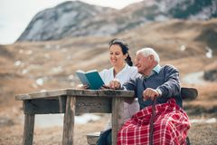 Nurse reading book to senior man outdoor. Smiling nurse reading book to senior men outdoor Stock Photos