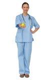 Smiling nurse in scrubs holding green apple Royalty Free Stock Photo