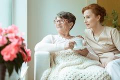 Nurse sitting with elder woman. Smiling nurse sitting with elder women on white sofa while drinking tea in living room Stock Image