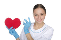 Smiling nurse with a syringe prick heart symbol Stock Photos