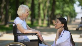 Smiling nurse talking with disabled elderly woman in park, rehabilitation center. Stock footage stock video footage