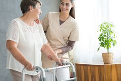 Old lady with walker. Smiling nurse in uniform helping old lady with walker during visit at home stock photography