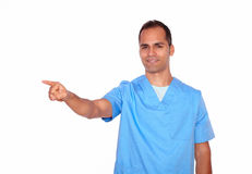 Smiling nurse in uniform pointing to his right Royalty Free Stock Image