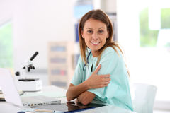 Smiling nurse working at hospital. Portrait of smiling nurse studying on laptop computer Stock Image