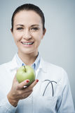 Smiling nutritionist with apple Royalty Free Stock Images