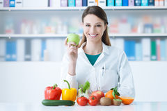 Smiling nutritionist in her office. She is holding a green apple and showing healthy vegetables and fruits, healthcare and diet concept Stock Image