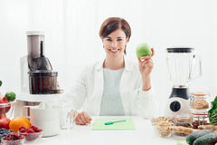Smiling nutritionist holding an apple. Smiling professional nutritionist holding an apple, she has healthy fruits, vegetables and juicers on her desk; healthy Royalty Free Stock Photos