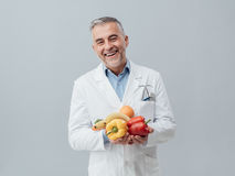 Smiling nutritionist holding fresh vegetables and fruit. Healthcare and healthy vegetarian diet concept Stock Images