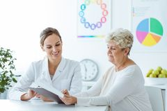 Smiling nutritionist showing diet plan. Smiling nutritionist showing personalized weight-loss diet plan to her senior patient Royalty Free Stock Images