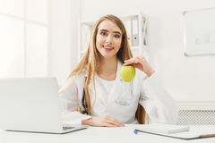 Smiling nutritionist woman with apple at office stock photography