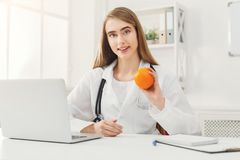 Smiling nutritionist woman with orange at office stock image