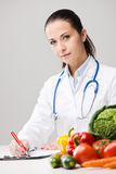 Smiling nutritionist writing medical prescriptions Royalty Free Stock Photo
