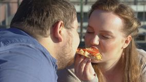 Smiling obese couple enjoying pizza taste, food passion, excess weight problem stock video footage