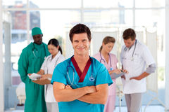 Smiling octor with his team in the background Stock Images