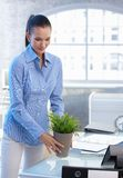 Smiling office girl moving plant pot Stock Photography