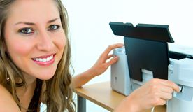 Smiling office girl with a printer and cable. Smiling office girl inserting a cable into a printer port royalty free stock photography