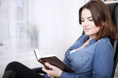 Smiling Office Woman on a Chair Reading a Book. Close up Smiling Pretty Young Office Woman Sitting on a Chair While Reading a Book Royalty Free Stock Photos