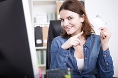 Smiling Office Woman at her Table Showing a Card Royalty Free Stock Image
