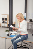 Smiling Office Woman on a Table Reading Notes Stock Photography