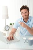 Smiling office worker at desk with phone handheld Royalty Free Stock Photos