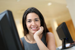 Smiling office worker in front of computer Stock Photography