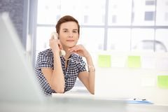 Smiling office worker on landline call Royalty Free Stock Image