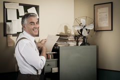 Smiling office worker searching for a file. Stock Image