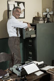 Smiling office worker searching for a file. Royalty Free Stock Photo
