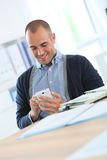 Smiling office worker taking a break with smartphone Royalty Free Stock Image