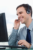 A smiling office worker using a headset Stock Images
