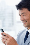 A smiling office worker using his mobile phone Stock Photography