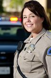 Smiling officer. A female police officer smiles with her patrol car in the background Stock Images