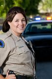 Smiling officer. A female police officer smiles while standing in front of her police car Stock Photos