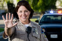 Smiling officer. A female police officer smiles as she holds up her hand to stop traffic Royalty Free Stock Images