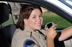 Smiling officer. A female police officer smiles while sitting her in patrol car Royalty Free Stock Photos