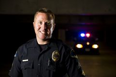 Smiling officer. A smiling police officer with his patrol car in the background Stock Images