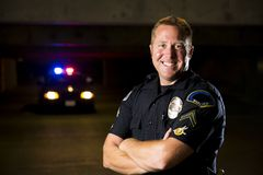Smiling officer. A smiling police officer with his patrol car in the background Royalty Free Stock Image