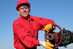 Smiling Oil Worker Turning Valve On Oil Rig. Portrait of a worker in action at pump jack oil well Stock Photo