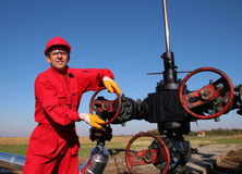 Oil and Gas Worker Wearing Protective Clothing. Smiling oil worker turning valve on oil rig. Oil pump jack in a field Royalty Free Stock Photo