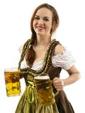 Smiling Oktoberfest waitress holding beers. Photo of a beautiful female waitress wearing traditional dirndl and holding two mass beer steins over white royalty free stock image